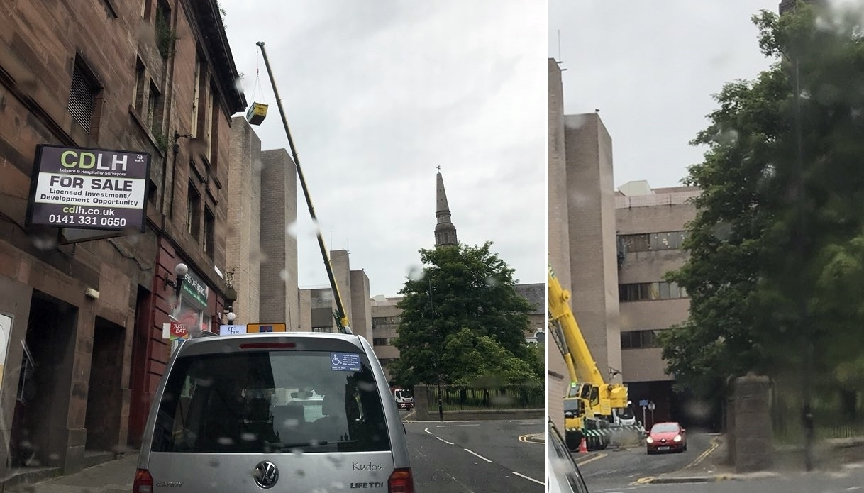 The taxi driver's images show the crane lifting a skip high in the air and near a road open to passing cars.