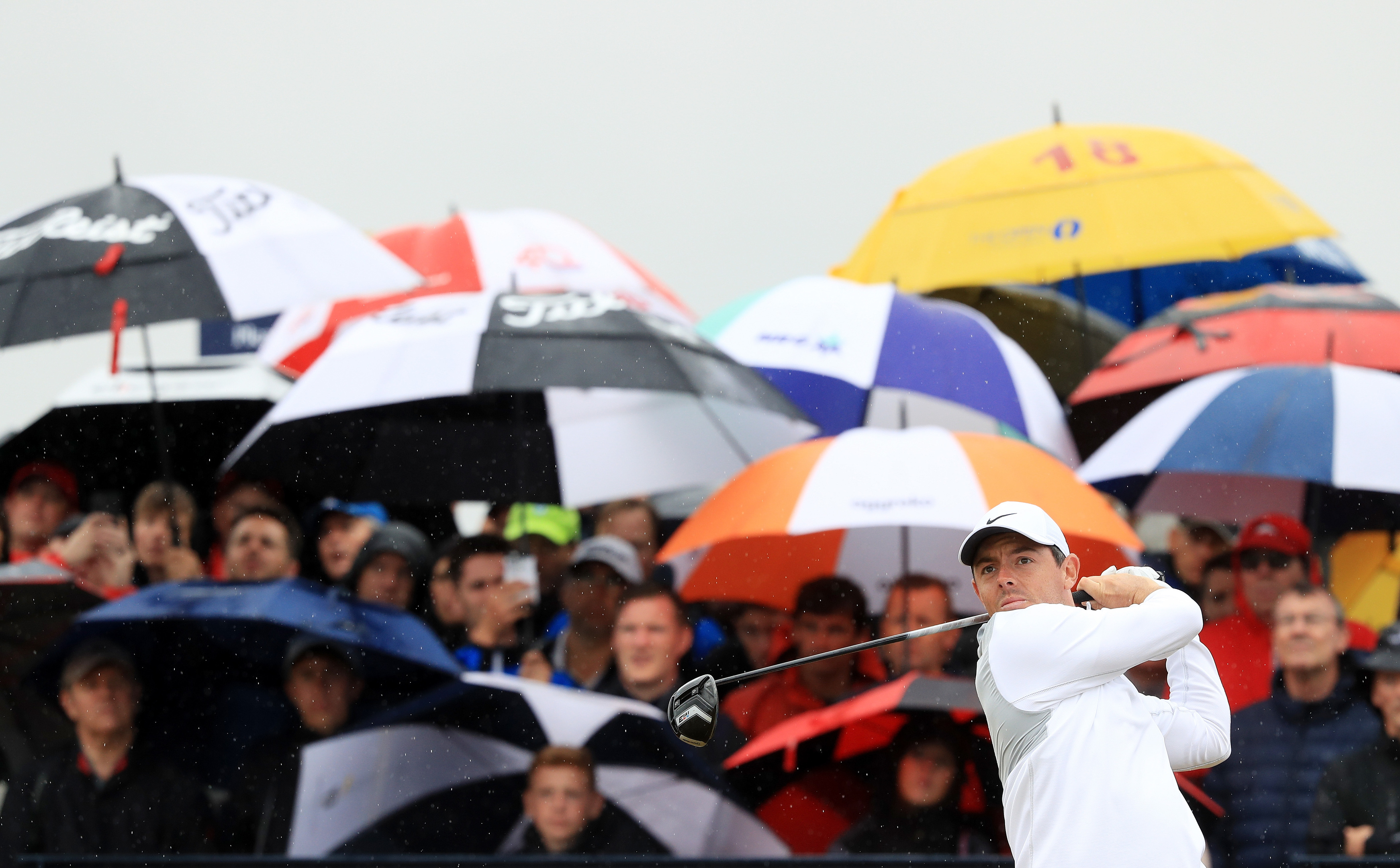 Rory McIlroy framed by the umbrellas during the morning rain in the second round at Carnoustie.