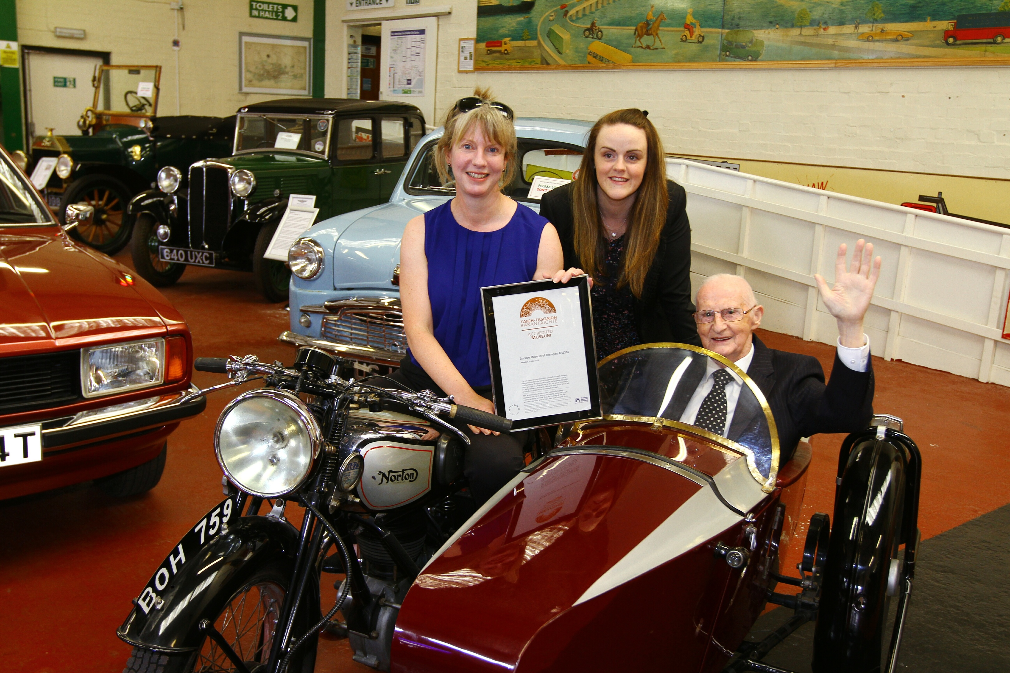 MSP Shona Robison with new chairman John Letford on a  1936 Norton bike with  Samantha Walker.