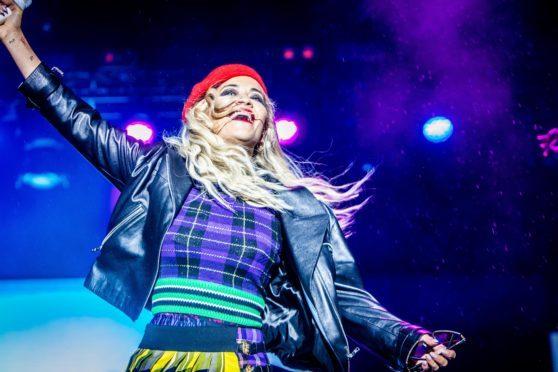 Rita Ora sings through the rain on Saturday night.