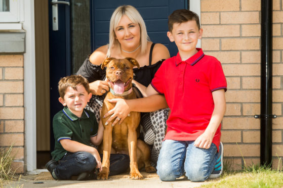 Clare Smith with her sons Flynn, 4, and Kiernan, 9, and Nala.