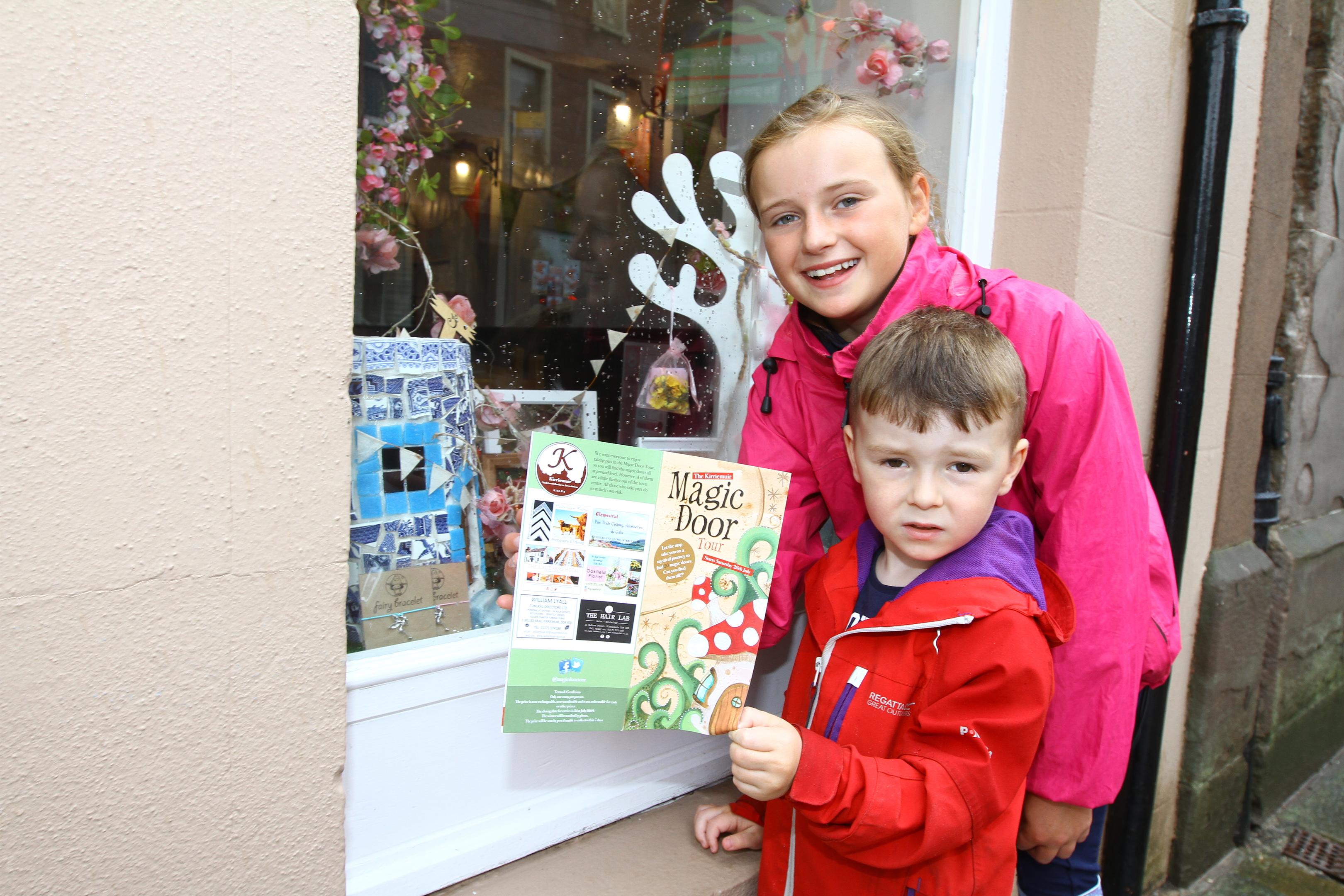 Courier Angus news-job CR0002748-   Mya Duncan Walker (11) & Cairn Hamilton (4) looking in shop windows to find the magic doors as part of the Magic Door Tour in Kirriemuir,saturday 28th july.