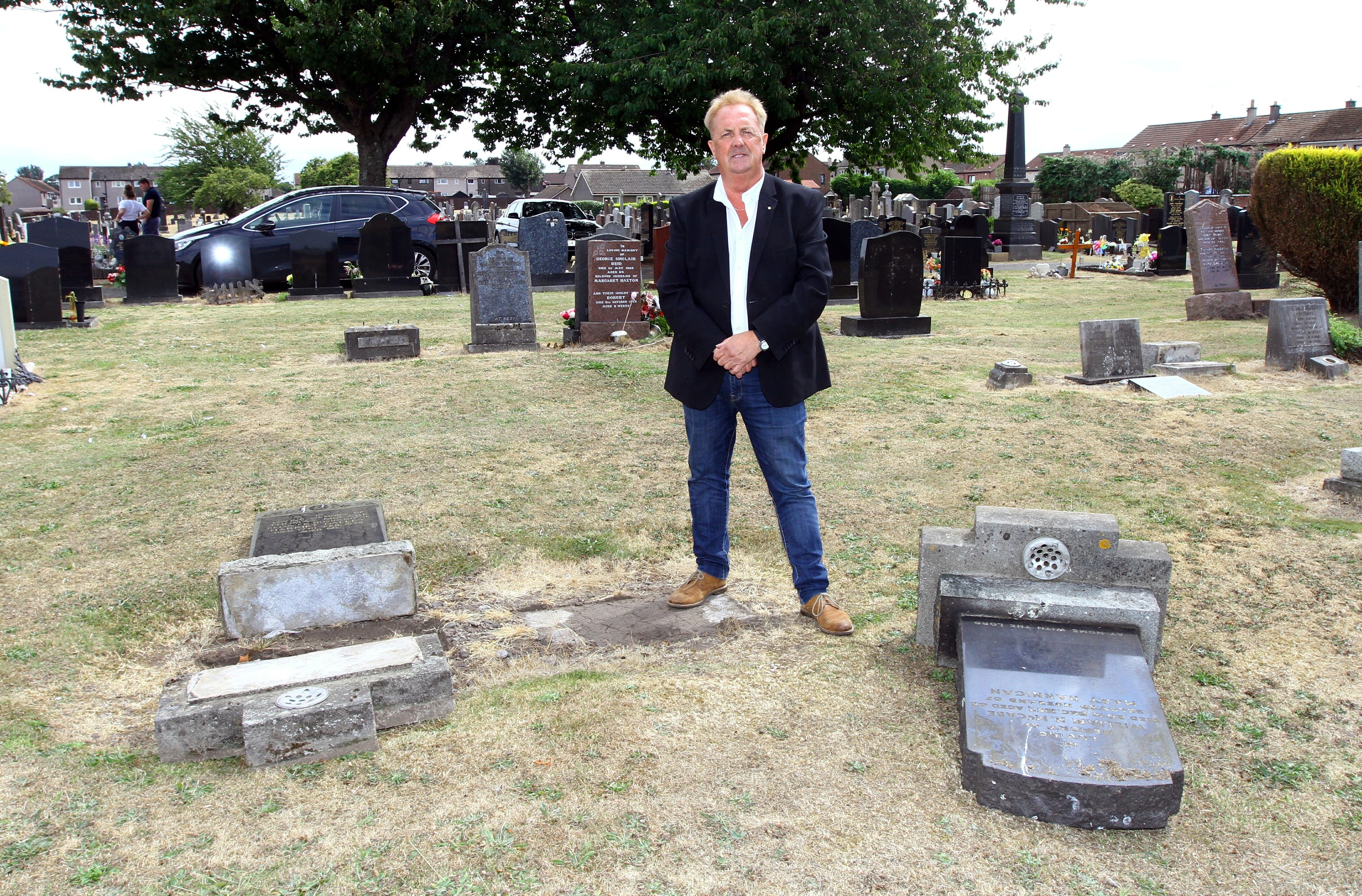 Councillor John O'Brien beside some of the damaged head stones.