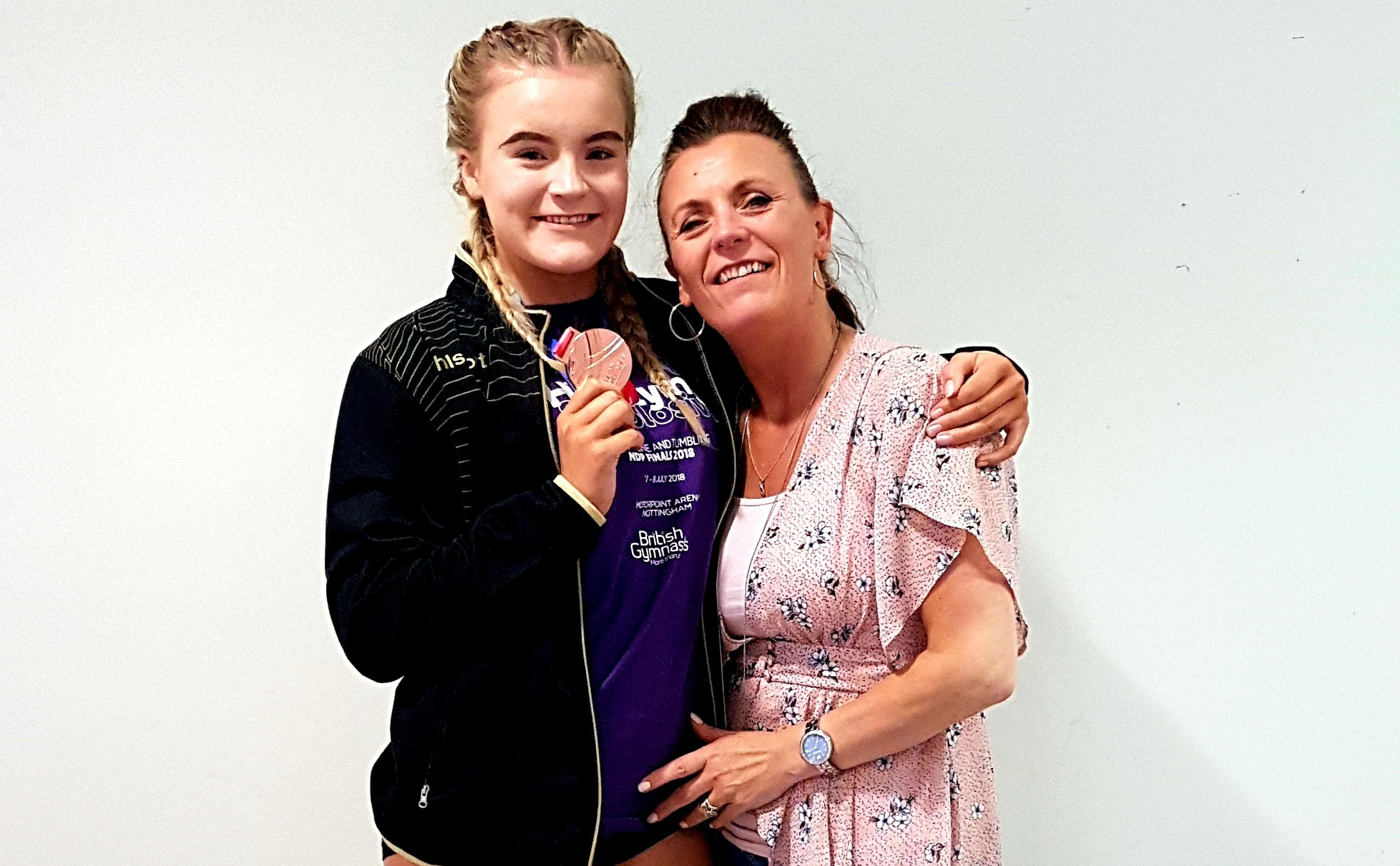 Tegan Gaffrey showing off her medal, accompanied by her mum, Cordelia.