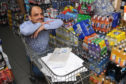 Hassan Majid Mirza in the Fairdeal Store,  Dundee, with a trolley containing documentation he has used in support of his application.