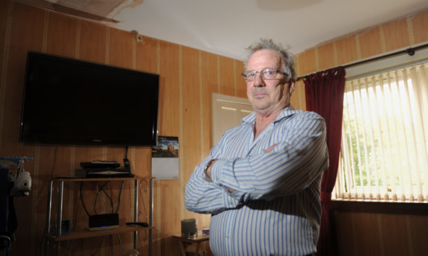 Robert Young in his living room which has been disrupted with dampness