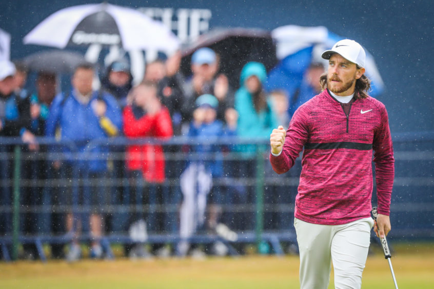 Tommy Fleetwood celebrating after holing a birdie putt.