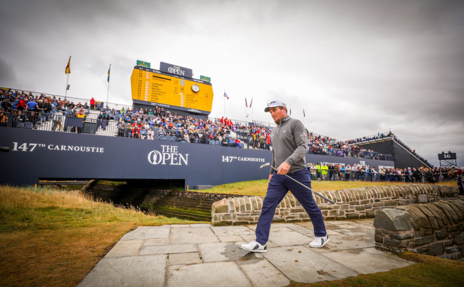 Ryan Fox crossing the Barry Burn in front of large crowds gathered around the 18th green as some of the big names finish their rounds.