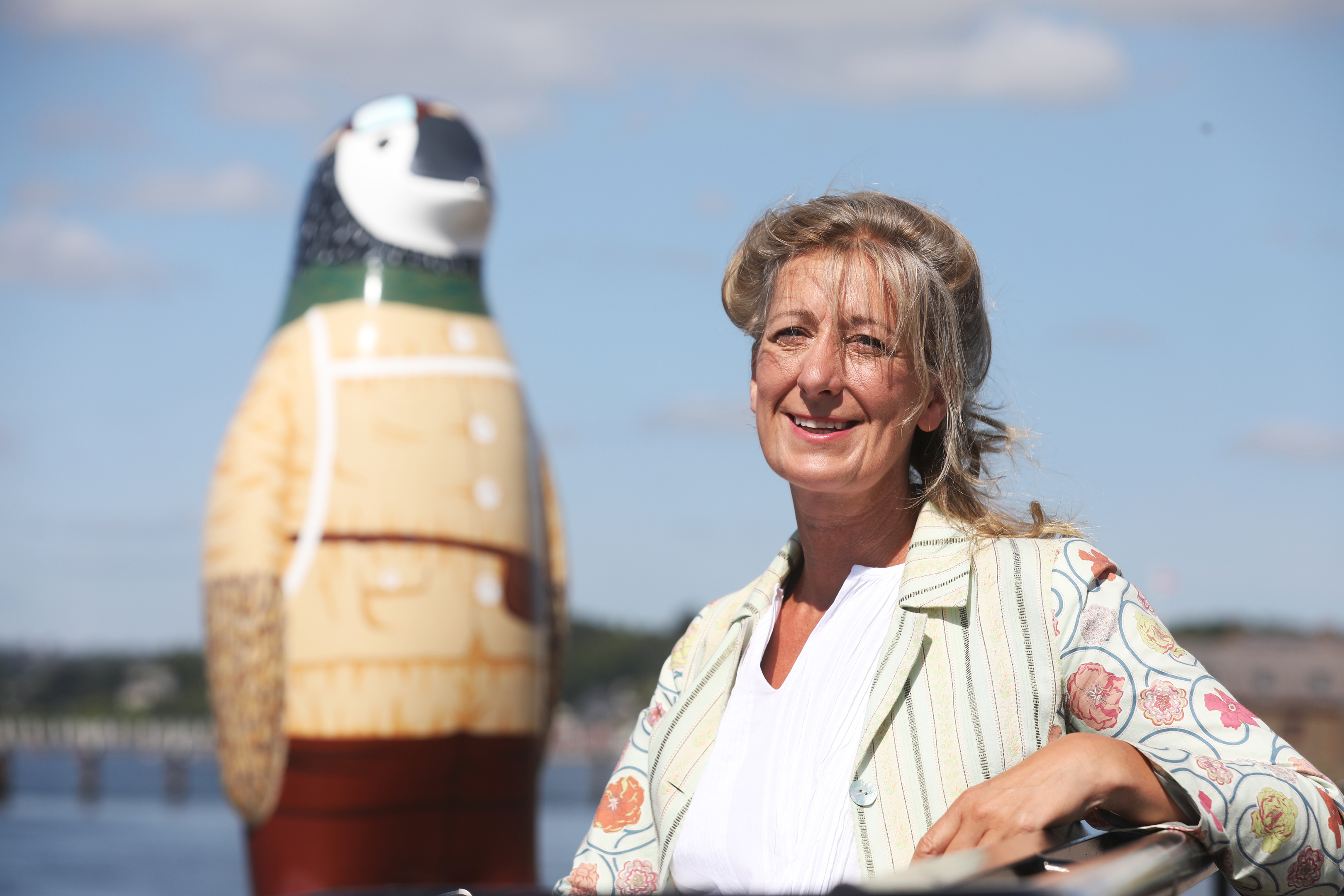 """Maggie's Dundee centre director Lesley Howells poses with her favourite penguin, the NHS sponsored """"Capguin Scott"""", at Broughty Ferry harbour."""