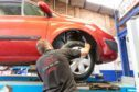 Wheels being examined on the Renault Megane by MOT Tester John Beveridge at Cupar Tyre and Autocentre