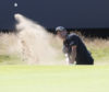 Kevin Kisner splashes out of the bunker at the final hole at Carnoustie on his way to a leading 66.