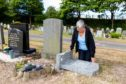 Mrs Ward examining the damage to her husband's headstone