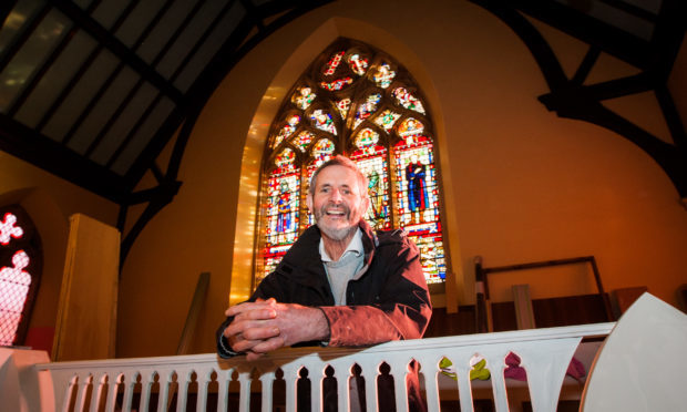 Willie Little with the stained glass window.