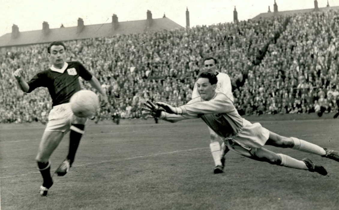Dundee United goalkeeper Sandy Davie saves from Dundee striker Alan Gilzean during a city derby at Tannadice in September 1962. Also pictured is United right-back Tommy Millar.