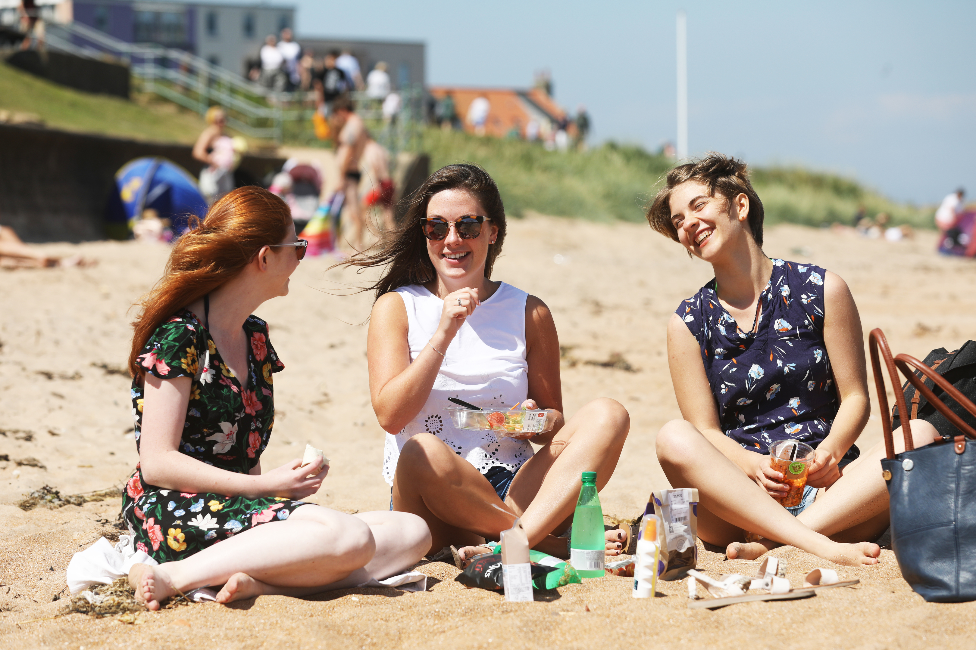 Catherine Mizen, 21, Gillian Anderson, 21 and Eileen Rapport, 21, students from St Andrews enjoying the weather down on the East Sands during the heatwave in 2018.