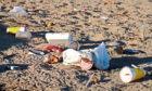 Trash left after an event on an urban beach.