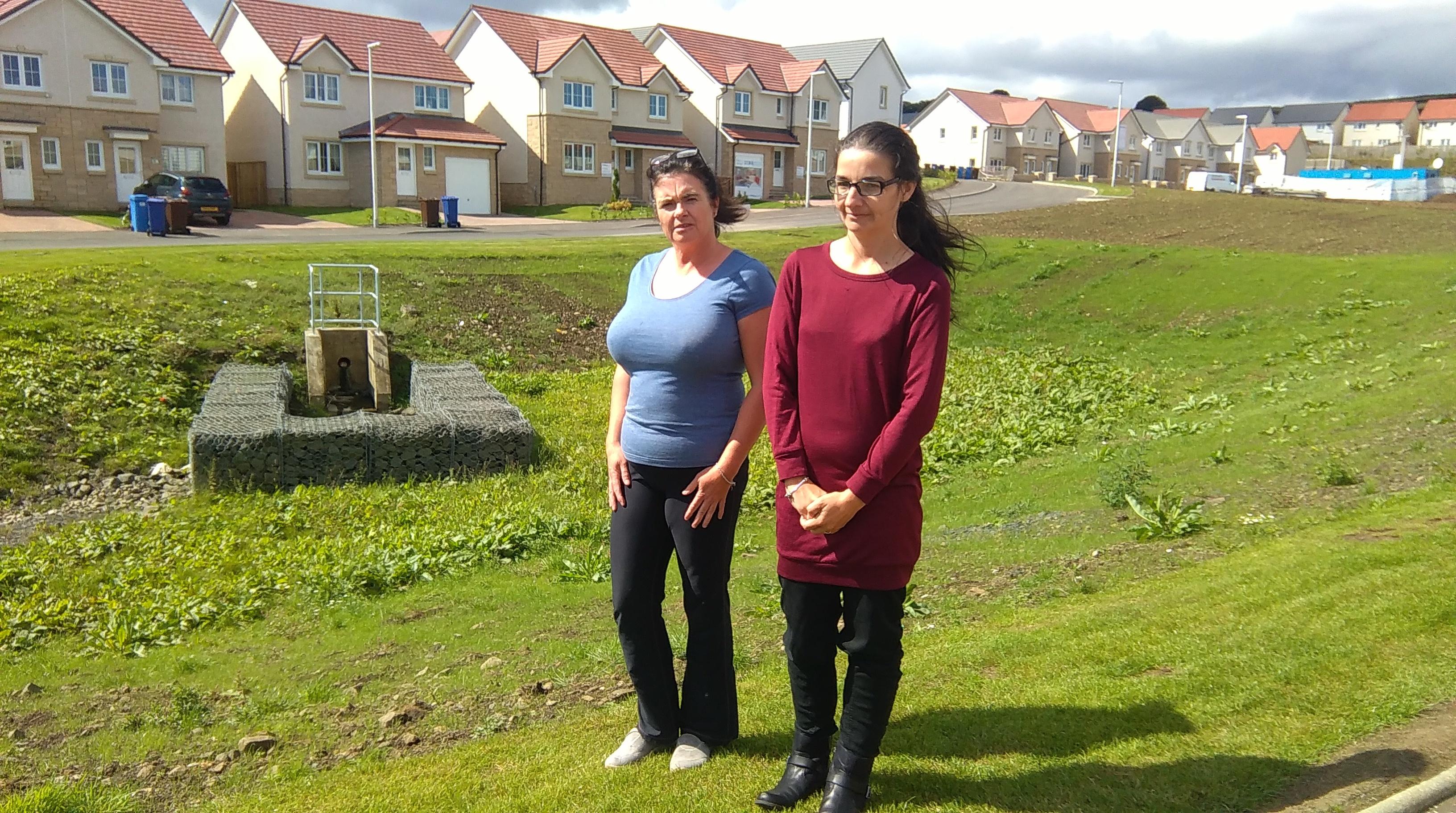 Residents Joanne Rankin, left, and Margaret Davidson beside SUDS pond.