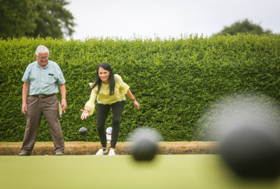 Sam Bryce showing Gayle how to bowl at Orchar Park bowling green.