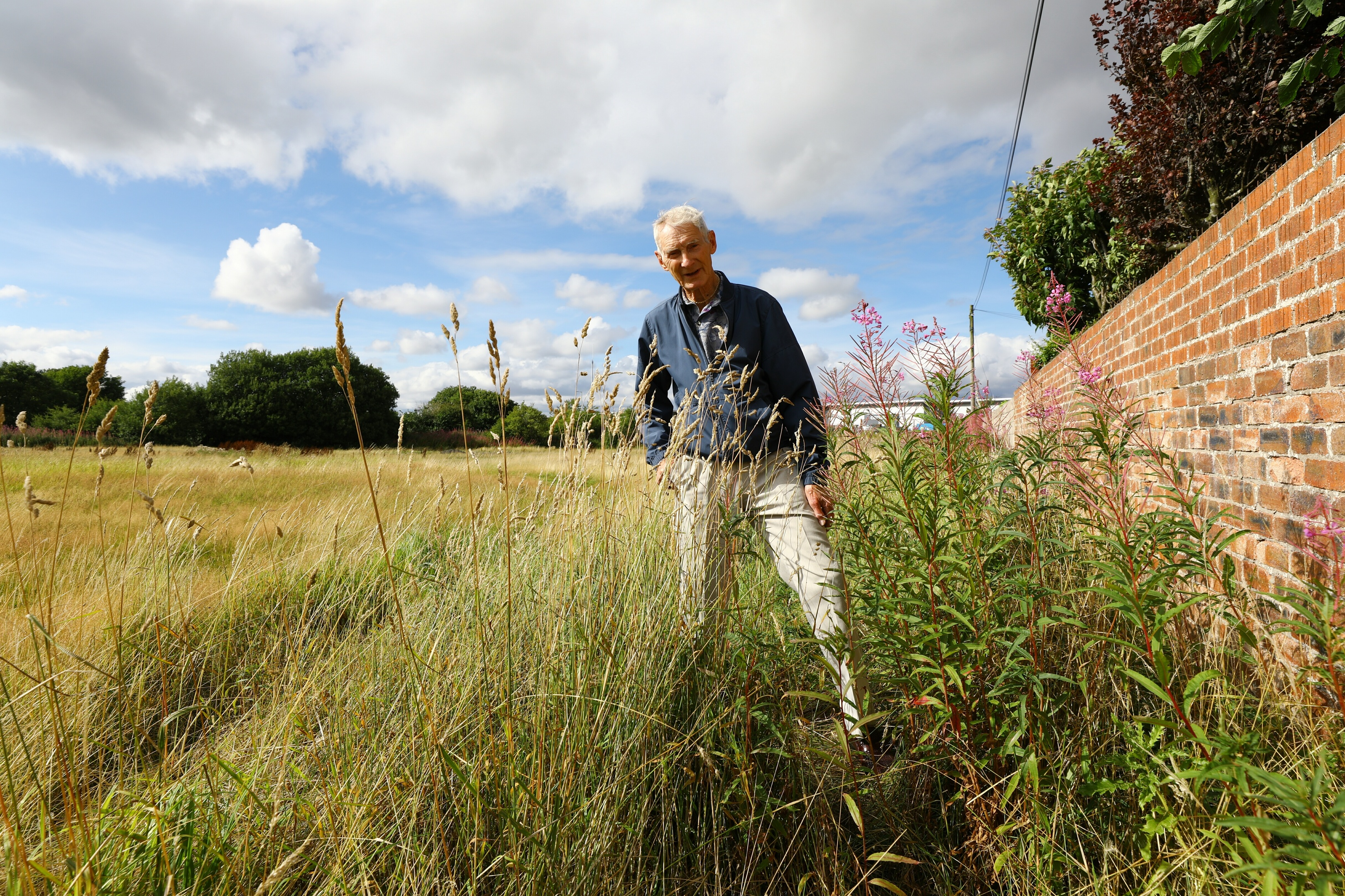 Sandy Mowat beside some of the overgrown weeds at the back of his house in Johnston Avenue.