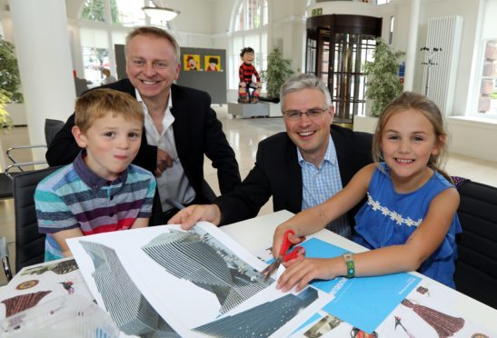Philip Long and David Thomson helping Jamie and Emily Thomson with their pop-up books.