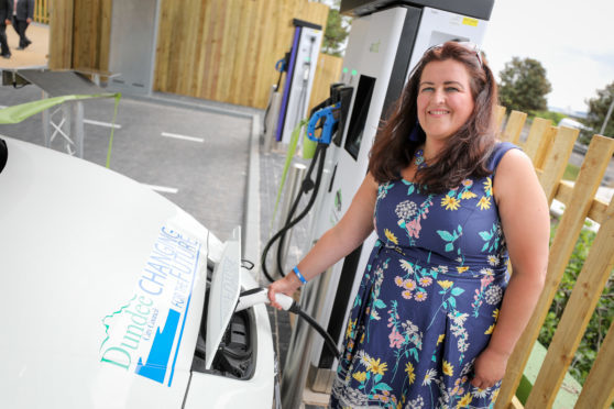 The council's city development convener Lynne Short by an electric vehicle in Dundee.