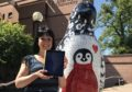 Suzanne Scott tries the AR app with her penguin outside Abertay University.