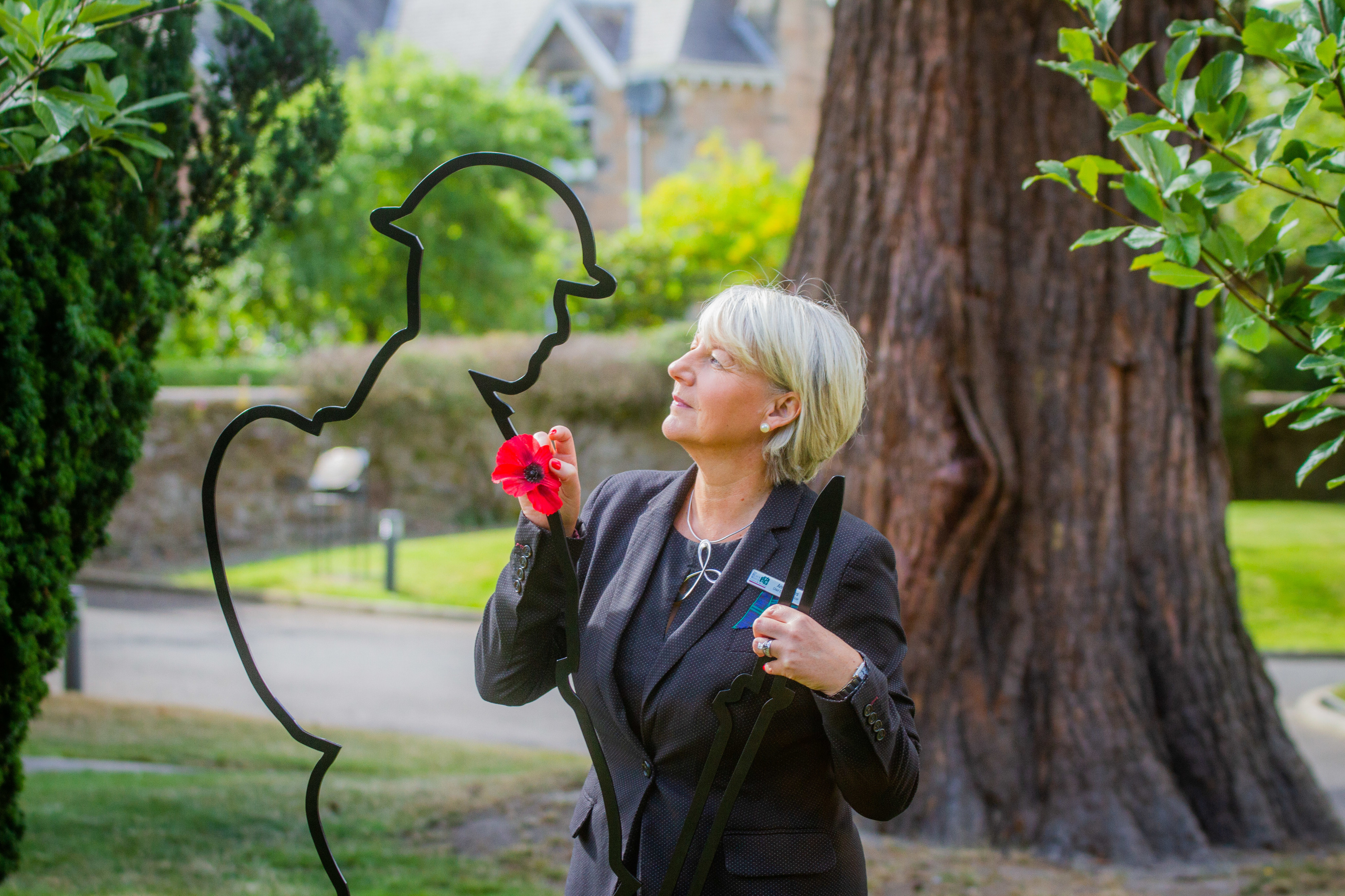 Anne Kinnes alongside the exterior silhouette Tommy sculpture.