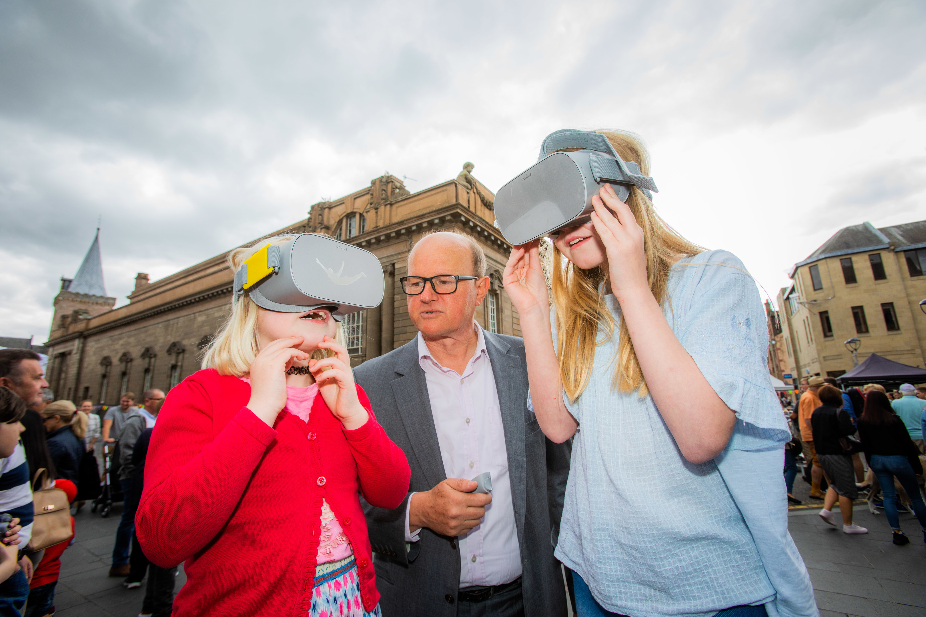 Sisters Flora Wylie (aged 8, left) and Erin Wylie (aged 12, from Perth) wearing the headsets alongside Chris Perry (from  international architectural firm Mecanoo).