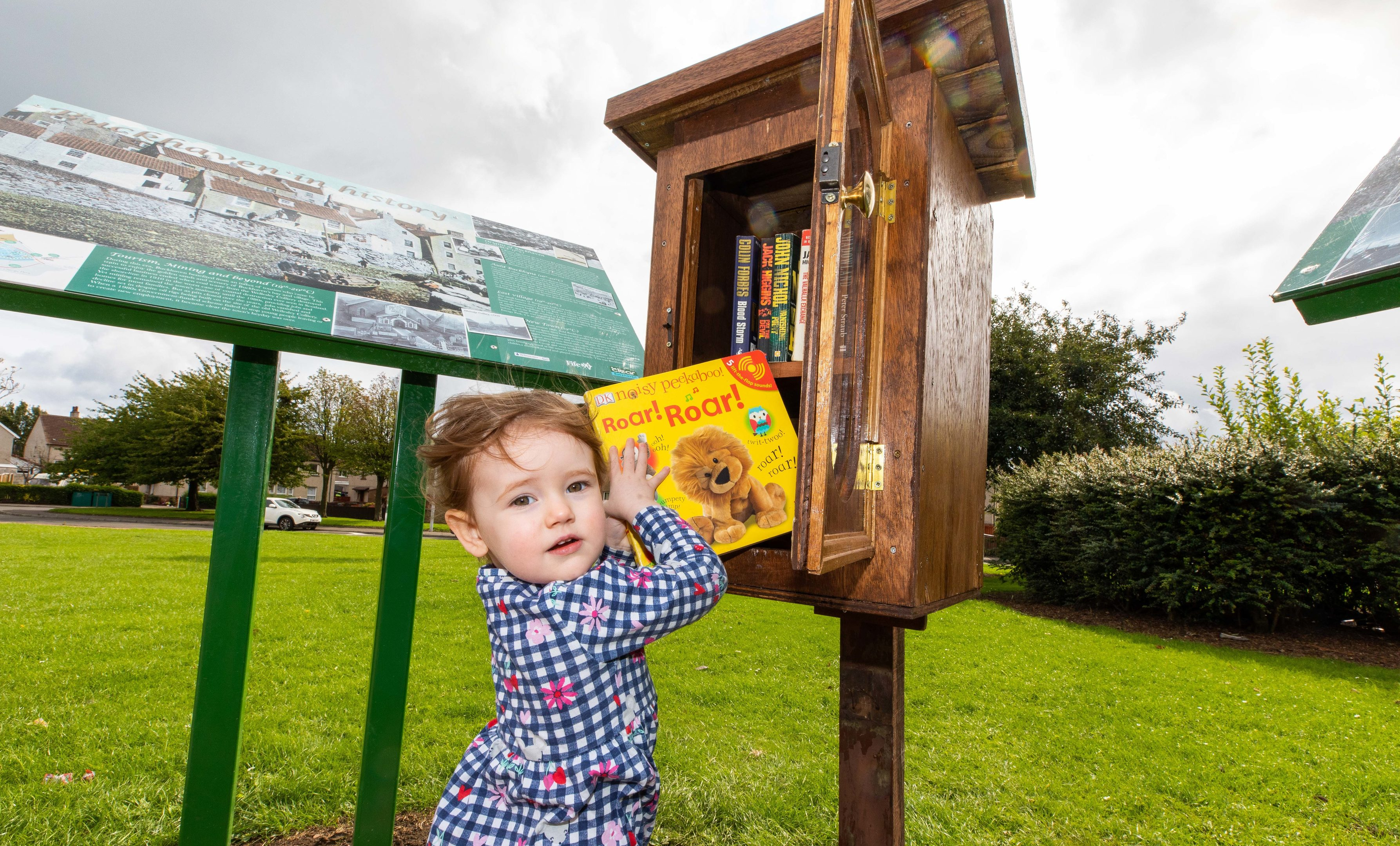 Two-year-old Carsyn Smart checks out a book from The Wee Library
