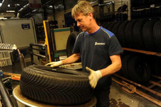 A Michelin Dundee technician carries out an inspection on a tyre.