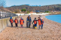 A beach is scoured for rubbish and plastics.