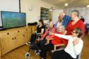 John Phillips, back centre, and Emma Ainsley, back right, both from Harmonious Place, with some of the residents watching the video, at Janet Brougham House in Dundee.