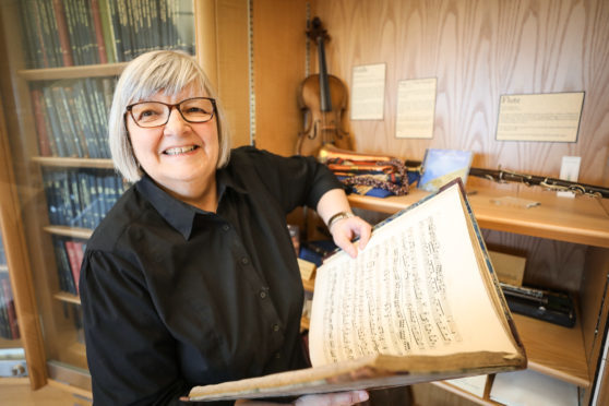 Sheena Wellington, of the Friends of Wighton, showing off one of the volumes being displayed.
