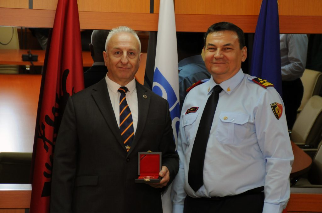 Adrian Nessel, left, receives his award in Albania