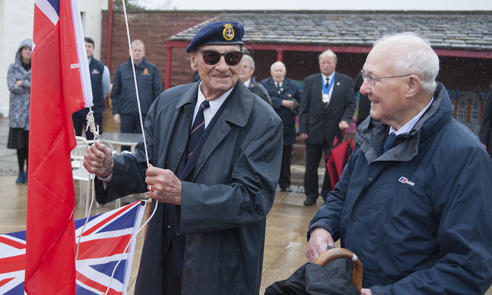 Retired Merchant Navy Captain Sandy Davidson raising the Red Ensign flag.