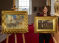 Carly Shearer of  Lyon & Turnbull holding James Watterston Herald's painting entitled 'Sunday Morning' with 'The Travelling Theatre, Buffalo Bill at Arbroath' on the left.
