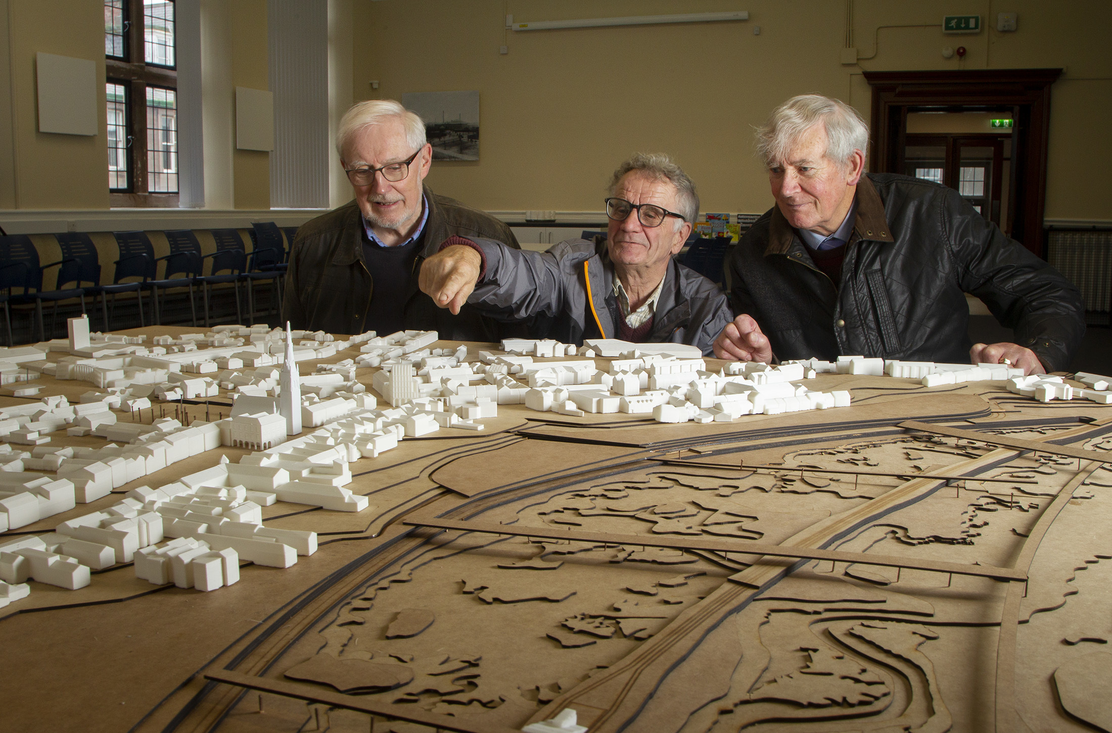 Sandy Munro, Raymond Sutton and John MacPherson of the Montrose Society study the 3D model on display at the town's library.