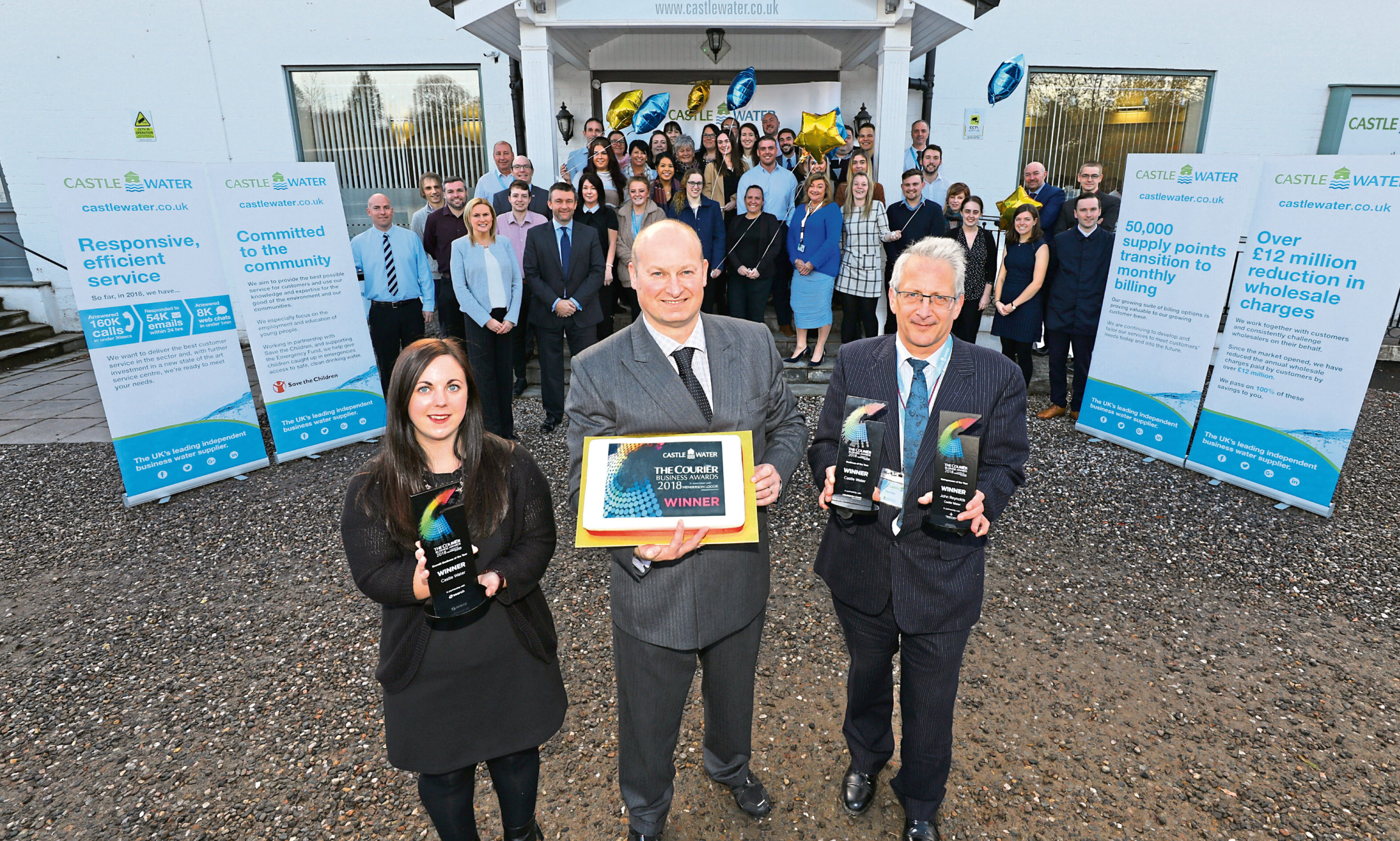 Mr Reynolds, front, centre, with a special cake, Laura Carr and Peter Strain, both holding the awards, and the firms staff. Picture: Dougie Nicolson.
