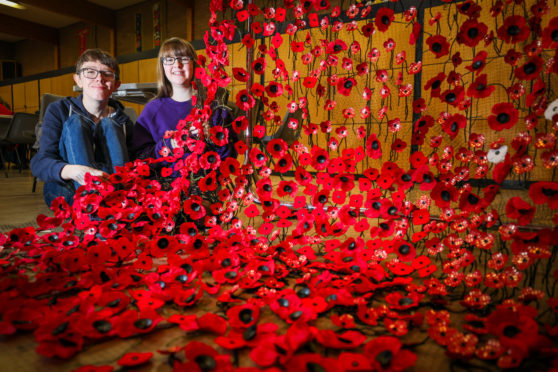 Stewart and Rebekah Lennon attaching poppies to netting to make up part of the Remembrance day display.