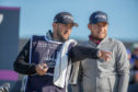 Tyrrell Hatton (r) and Scottish caddie Mark Crane plot their way to a 66 at Carnoustie yesterday.