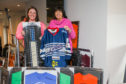 Clare Jamieson from Alzheimer Scotland and Amanda Kopel with some of the shirts sold at auction.
