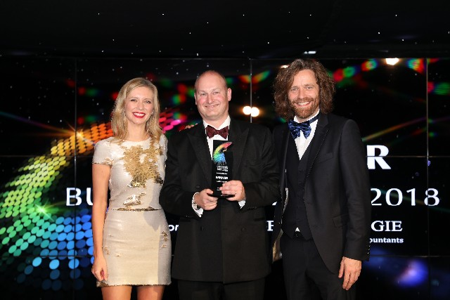 Castle Water chief executive John Reynolds accepts the Business of the Year prize presented by Rachel Riley and David Smith of Henderson Loggie.