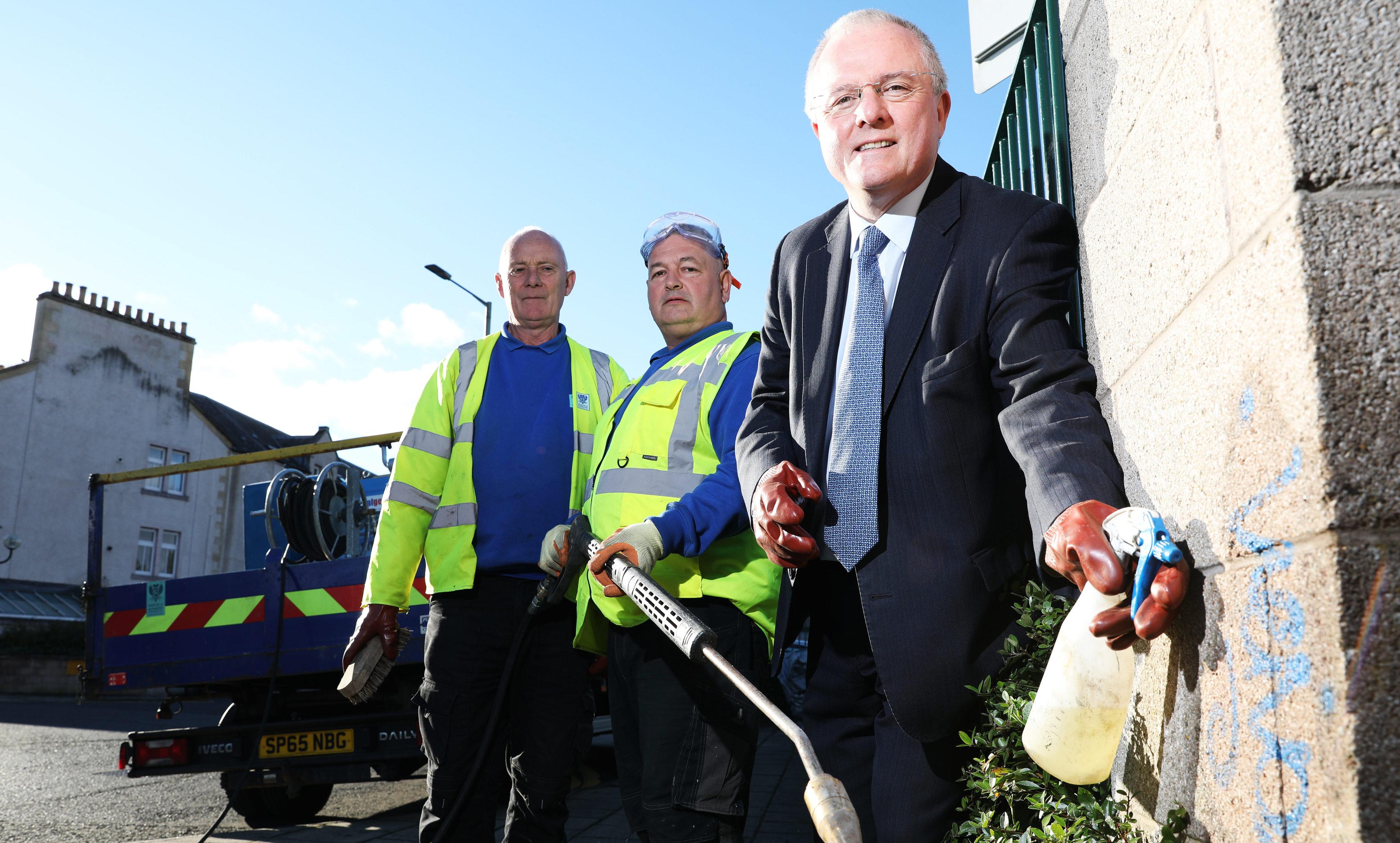 Peter Barrett helping clean up graffiti in the city.