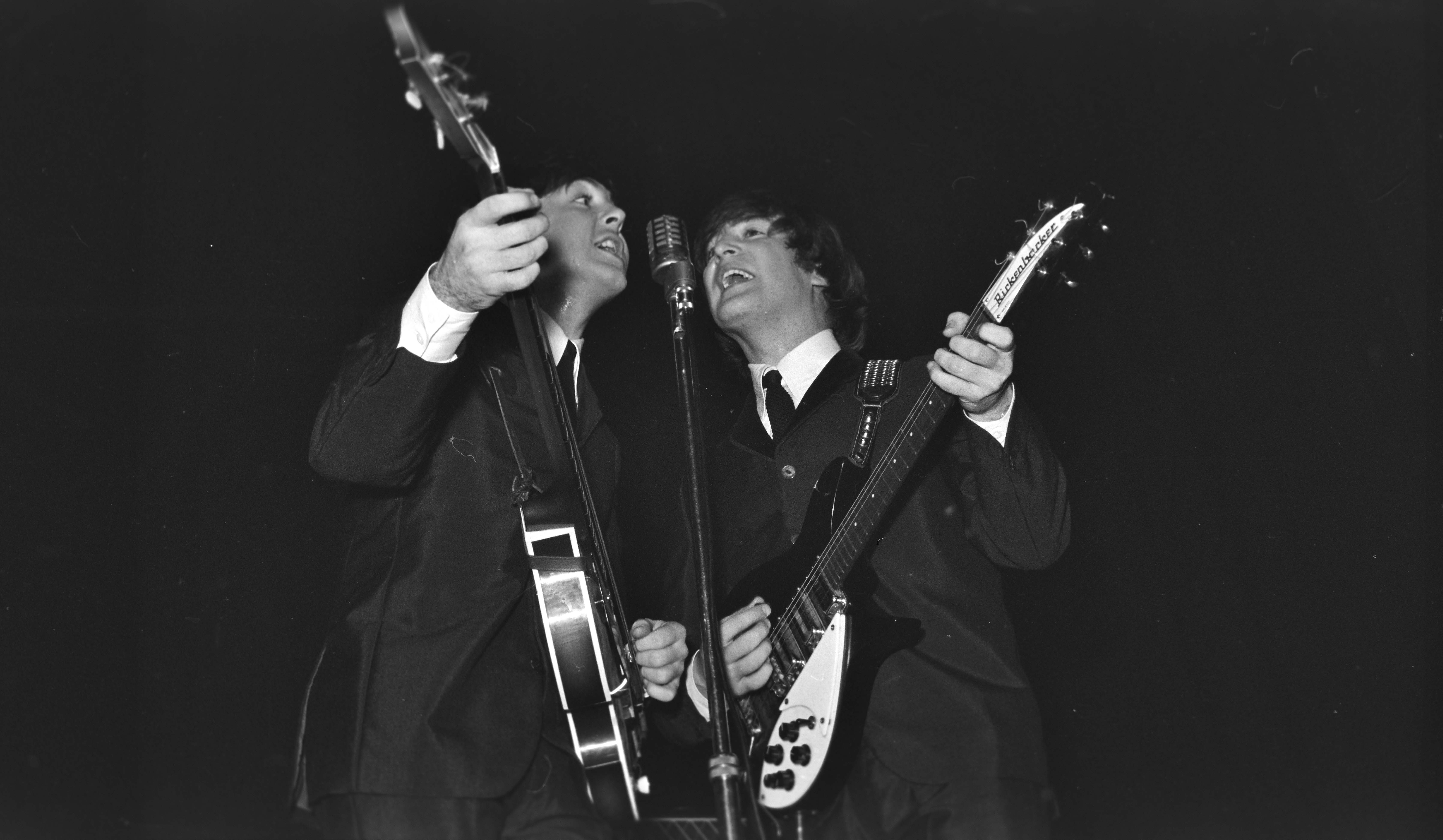 Paul McCartney and John Lennon on stage at the Caird Hall in 1964.