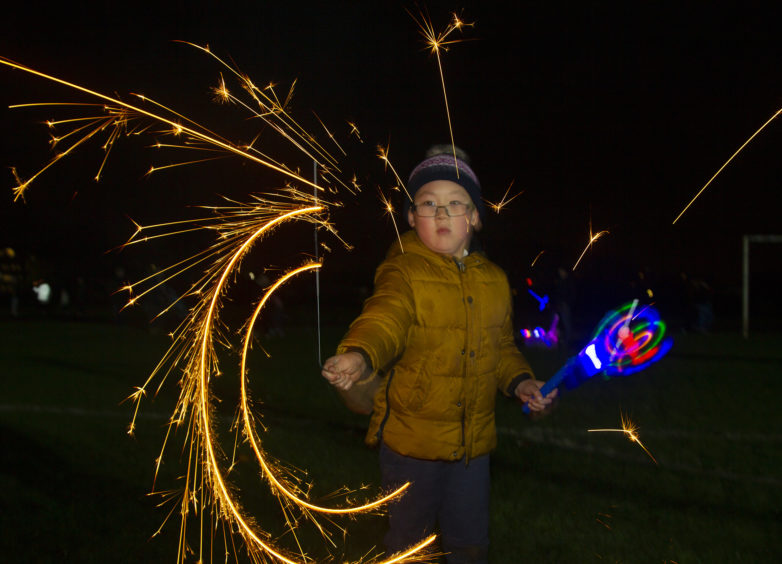 A youngsters with a sparkler at the Lochee Park fireworks.