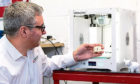 Andy Simpson, Managing Director of Angus 3D Solutions, checking a 3D-printed part.
