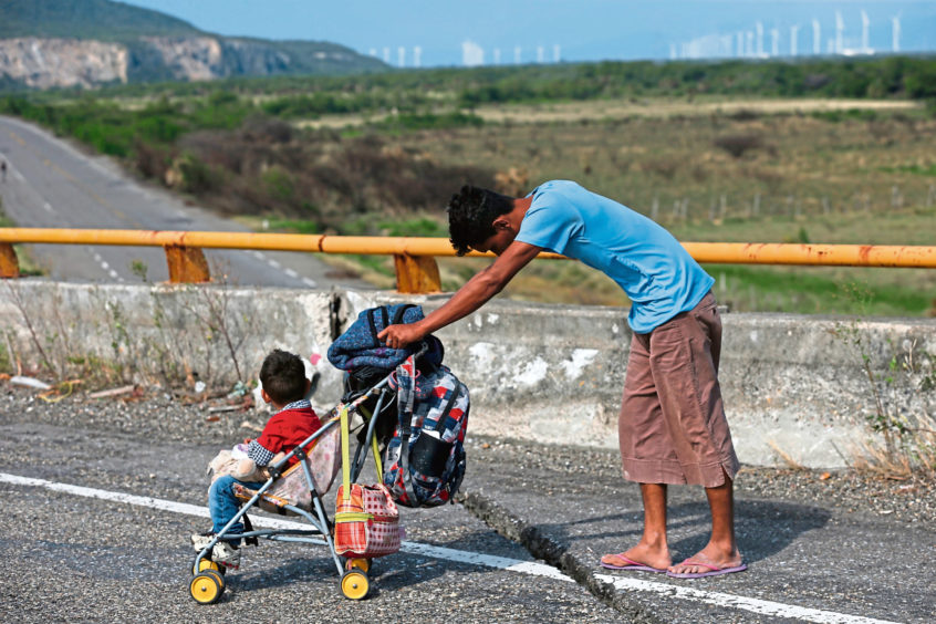 A man pushes a child in a stroller along the highway as a thousands-strong caravan of Central Americans continues its slow journey toward the U.S. border, between Niltepec and Juchitan, Oaxaca state, Mexico.