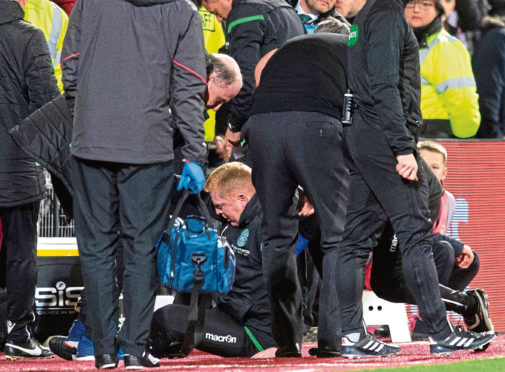 Hibernian manager Neil Lennon is helped to his feet by Hearts manager Craig Levein and a member of the Hibernian backroom staff after appearing to be struct by an object from the crowd during the Edinburgh derby.