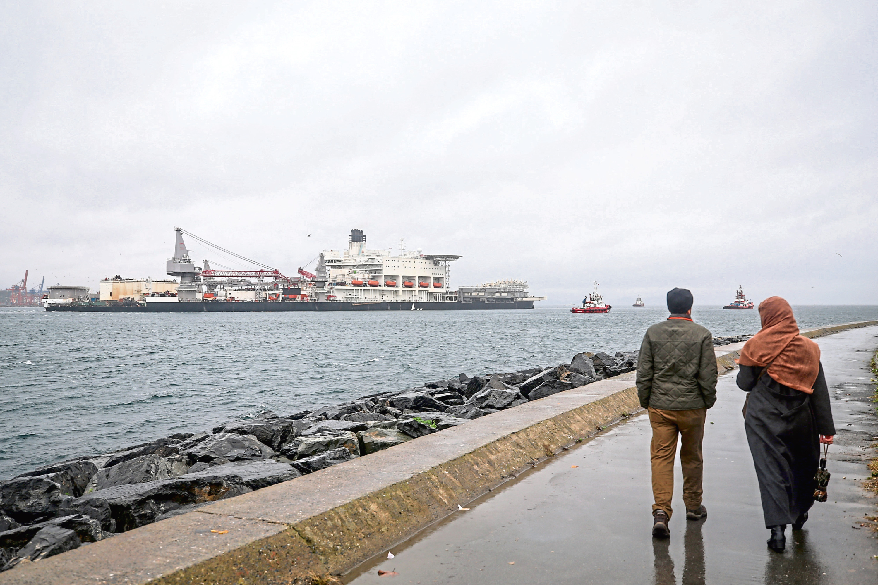 A man and a woman walk through the coastline as the Pioneering Spirit, the world's largest construction ship, passes through Bosphorus to lay natural gas pipe to the deepwater of TurkStream in Istanbul, Turkey on November 22, 2018.