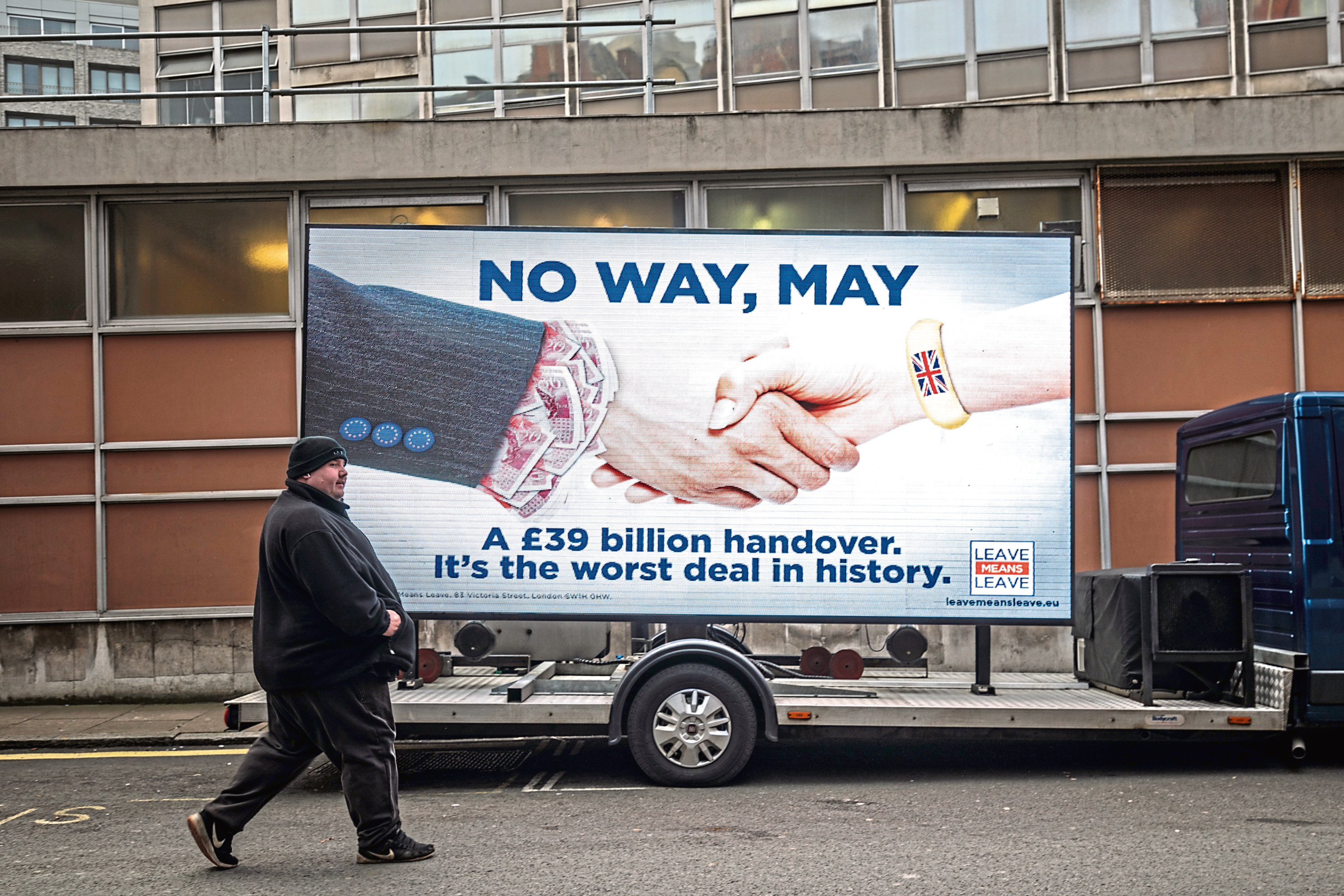 A man walks past an electronic billboard during the launch a new 'Leave Means Leave' campaign against British Prime Minister Theresa May's Brexit agreement on November 27, 2018.